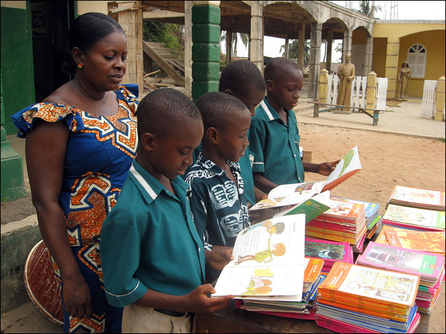 Pupils of Elmina Catholic Boys' Primary School readng the donated books